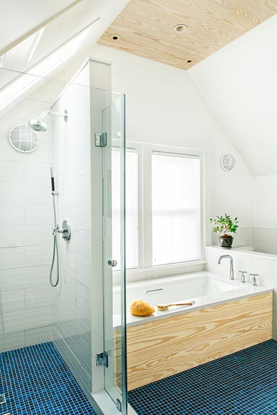 a tub with a view and a shower under the sloped ceiling in the remodeled washroom of the renovated this old house tv cambridge project