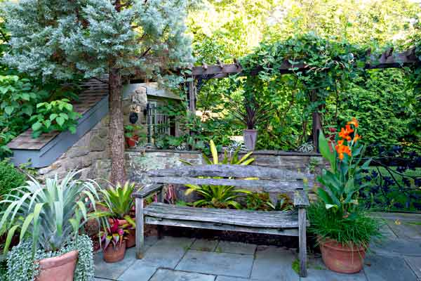 yard with outdoor rooms, bluestone patio with bench, container plants, stone wall, arbor