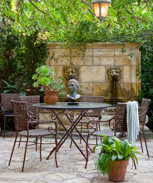 after yard remodel patio with dining set, container plants, lions head fountain, hanging lantern, statue bust