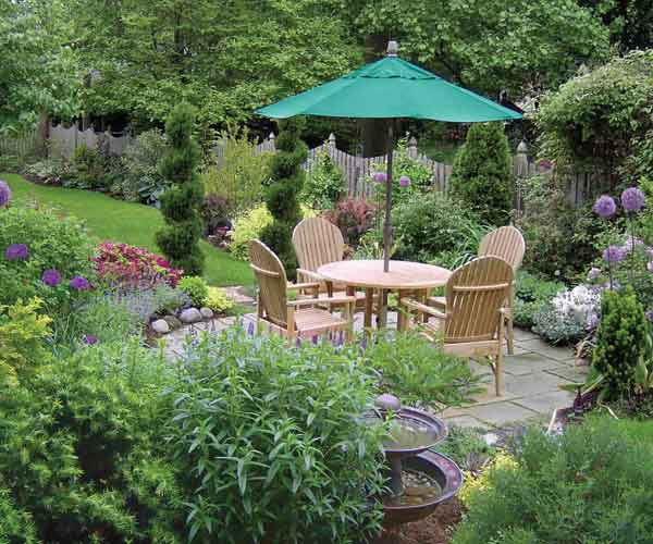 after yard remodel patio with dining set and umbrella, container plants, fountain, fence