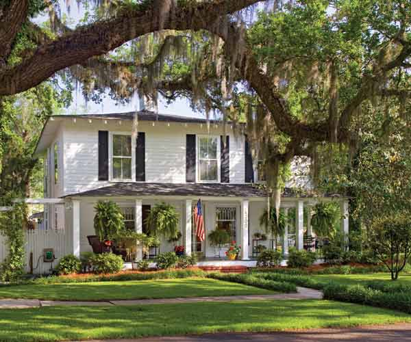 white craftsman house with wraparound porch, whole house remodels of historic houses