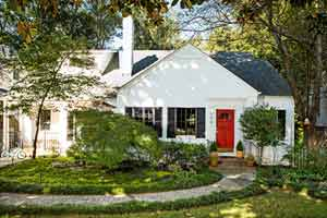 house exterior with red door, white siding, and a lush, manicured lawn