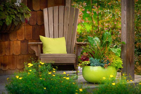 porch with adirondack chair and bright container plant, uncommon container gardens