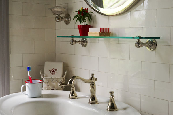 the corner of a clean, bright bathroom with white subway tile, an open glass shelf below a mirror, and a pedestal sink with a cup holding a toothbrush set on one side