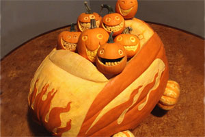 stack of small, carved pumpkins driving a carved-pumpkin car