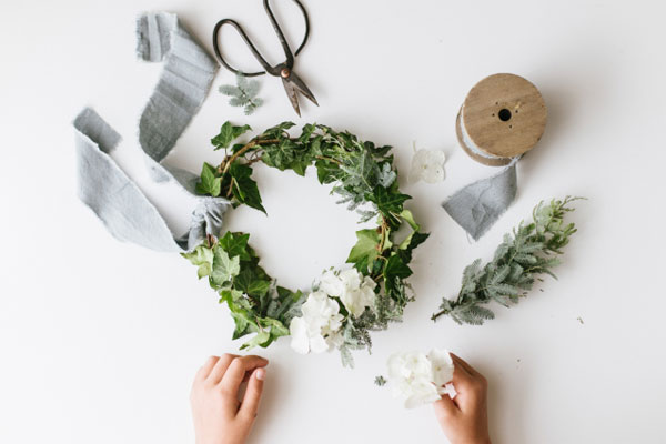 hands holding white flowers over a partially completed, green holiday wreath with bits of ribbon and a pair of scissors also in the picture