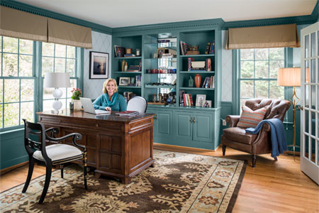 homeowner sits in a newly remodeled home office, with a laptop open on the desk. a warm-toned area rug covers much of the hardwood floor, with it's colors echoed in the window treatments and furniture. The book cases and walls are painted a deep teal