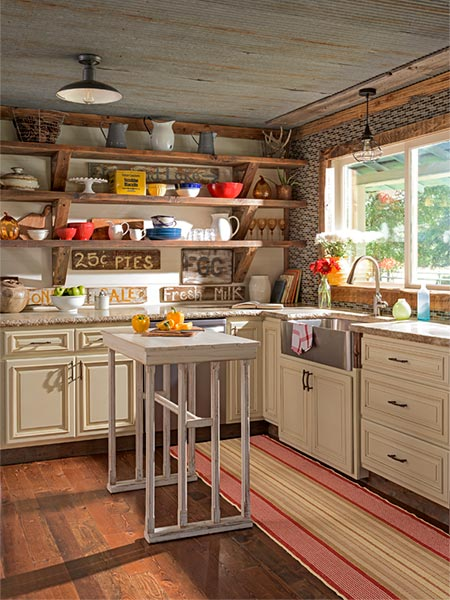 farmhouse style kitchen with plank flooring, corrugated steel ceiling, wood cabinets, stainless steel sink, and rustic open shelving covered in objects like pitchers, old tins, and serving plates