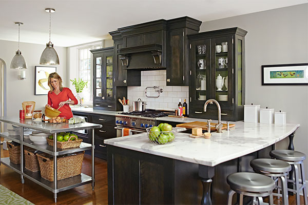 a person is stirring the contents of a bowl, standing at a stainless steel island in a bright, modern, open kitchen. Pendant lights hang overhead, and a large, L-shaped marble counter wraps back under dark custom cabinets