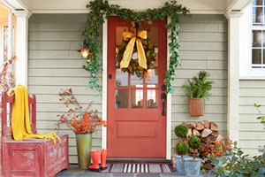 decorated entryway of a green, white, and blue house. the porch is blue stone and brick, the door and storage bench to the side are red, and festive green garland, wreath, and plantings surround the entrance