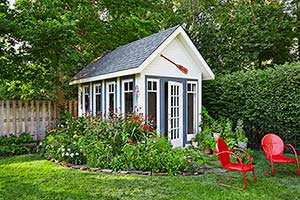 yard with white and blue potting shed with gray roof and salvaged windows surrounding by flowering plants and with red lawn chairs nearby