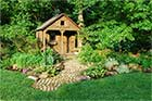 outdoor shed in backyard with brick paver patio and landscaping garden around it