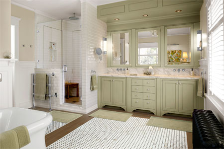 bright, open, modern bathroom with black, white, and brown floor tiles. Green built-in cabinets run the length of the double-bay sink, and a standing shower stall with glass door abuts the sinks. A tub and radiator visible in the foreground