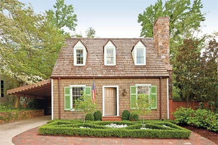 remodeled cape cod two story house set in a manicured lawn. the house has one large field stone chimney on the right side, and an american flag hung to the left side of the door. gree shutters hang on the downstairs windows