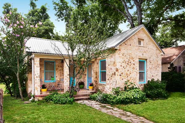 a lovely limestone cottage bungalow with metal roof and blue trim on the windows, set in a lush, green yard, surrounded by small trees