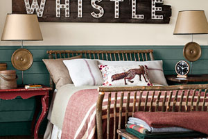 rustic look bedroom with a bed made from rough-look vertical logs. A faded-paint wooden chest is set at the foot of the bed with stacked wool blankets on top. A train sign hangs on the wall behind, with lamps on side-tables to either side