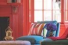 living room with bright red paint on the walls and eclectic furniture