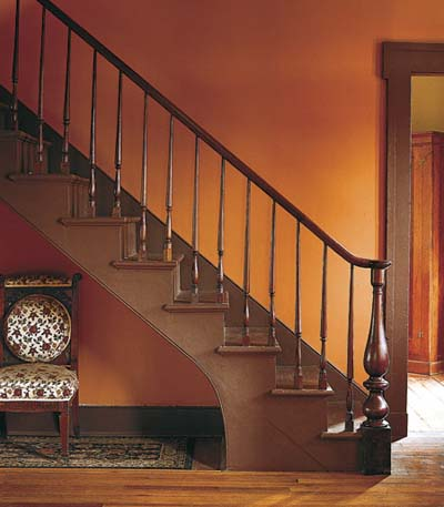 orange walls and walnut staircase