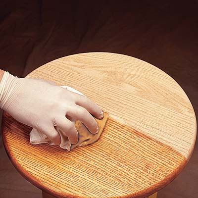a latex-gloved hand wipes a polyurethane-soaked cloth across a tabletop