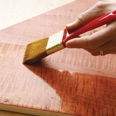 applying polyurethane to a tabletop surface with a brush