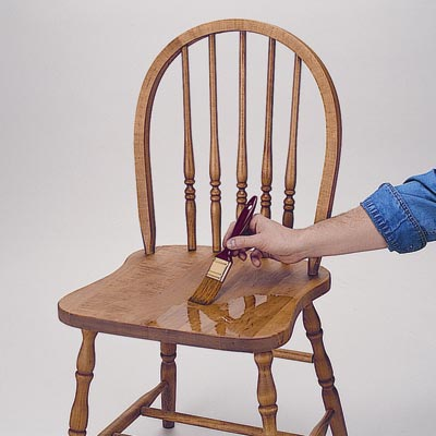 man applies polyurethane to a chair seat using a brush