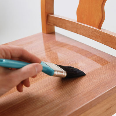 person applies polyurethane to a chair seat with a brush