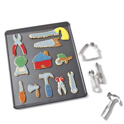 a cookie baking sheet with tool shaped cookies and cookie cutters to the side