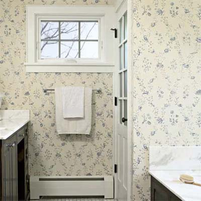 paneled door hiding the bathroom in this remodeled shingle-style cottage