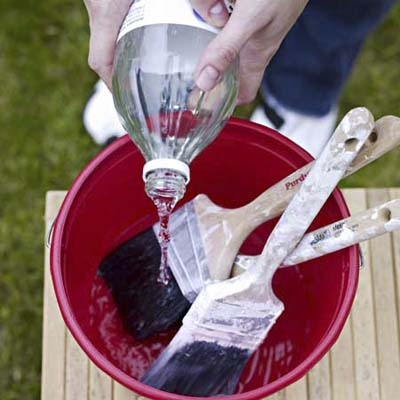 cleaning brushes in a bucket of vinegar