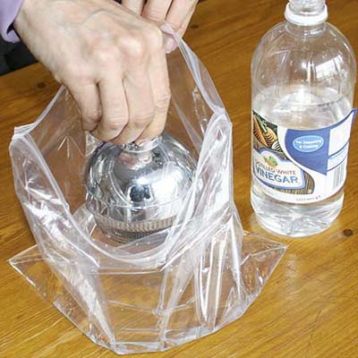 dipping a shower head into a plastic bag filled with vinegar