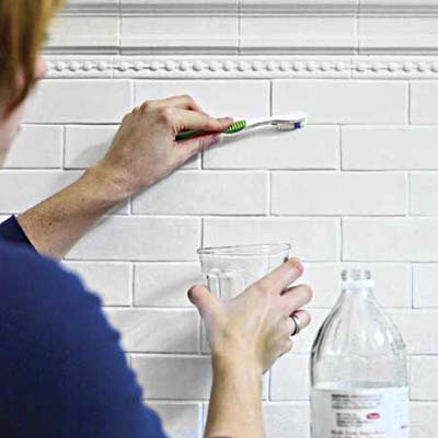 scrupping grout with toothbrush dipped in vinegar