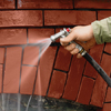 washing away mortar debris from a brick wall
