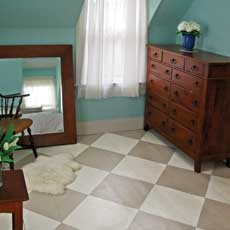 a bedroom painted in a beige and white diamond checker pattern
