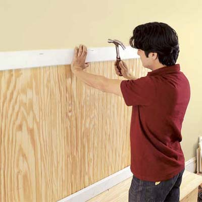 attaching the trim to hide the beadboard edges on the mudroom bench