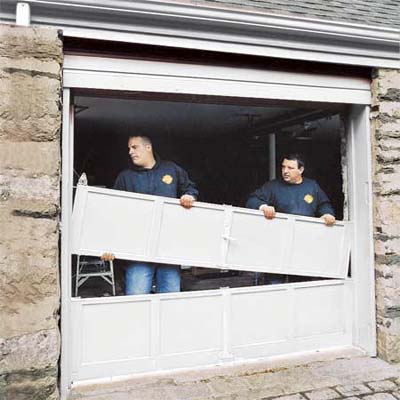 two workers dismantling a common overhead garage door