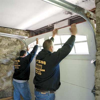 two workers lifting the last door section into place