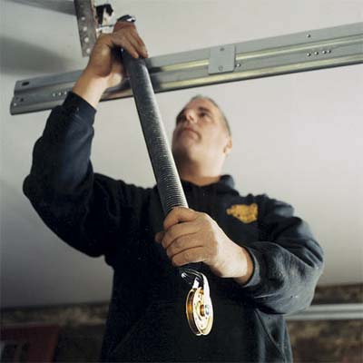 worker installing one of the garage door extension springs to the garage ceiling