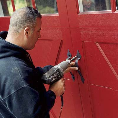 worker attaching the hardware to the outside of the new carriage-style doors