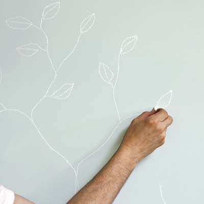 hand shown sketching branches with leaves on a wall with chalk
