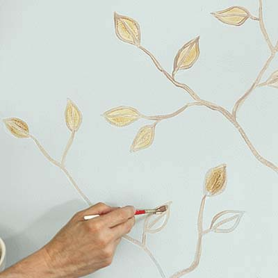 gold paint applied to leaves sketched on a wall