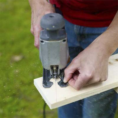 hands using a jigsaw to cut a wood board to shape for the box, top or legs of the pet ramp
