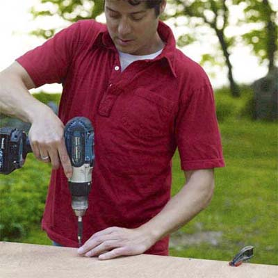 man using a drill driver to screw attach the bottom to the pet ramp box