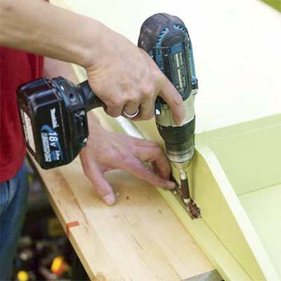 hands using a drill driver to attach a block to the underside of the lid