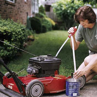 Woman emptying her lawn movwer's gas tank into an old coffee can