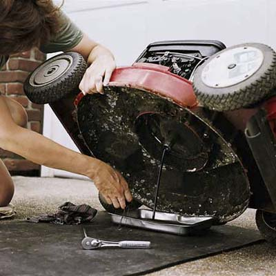 Drain the mower's oil into a pan; be sure to spread tarp beneath for easy clean-up