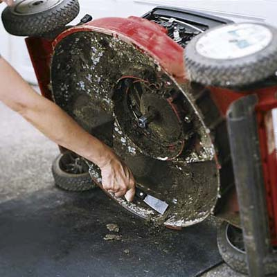 Clean the undercarriage of the mower, scraping away debris with a putty knife