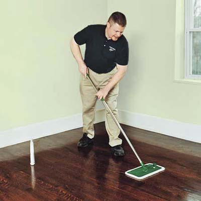 man with mop cleaning a wooden floor