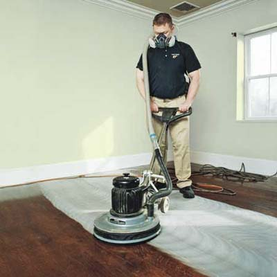 man scuff-sanding a wooden floor with a buffer to prep before refinishing