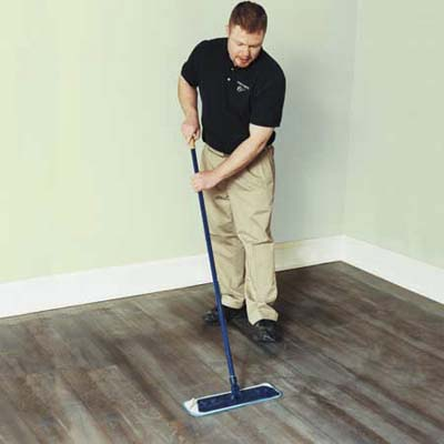 man dry-tacking a freshly buffed wooden floor with a microfiber cloth attached to a flat mop