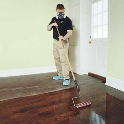 applying polyurethane with long-handled roller to a freshly buffed wooden floor